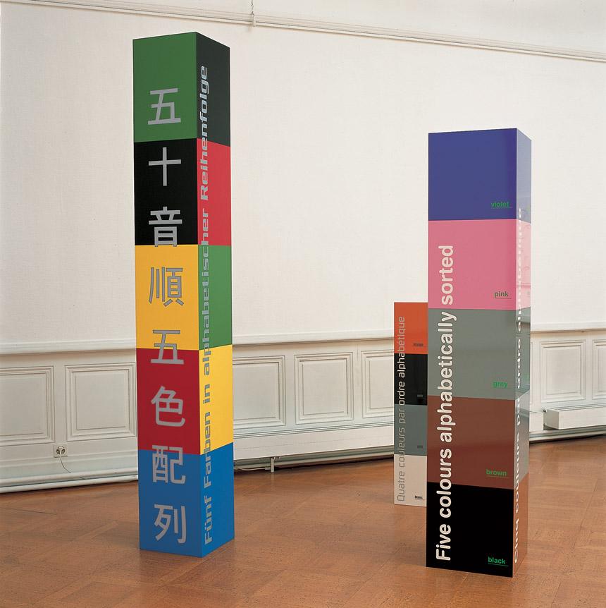 Database totem II (allemand, anglais, français, japonais), 2001 acrylique sur bois / acrylic on wood – 250 x 35 x 35 cm. Database totem I, (allemand, anglais, français, italien), 2001 vinyle autocollant, verre acrylique / vinyl sticker, acrylic glass – 200 x 40 x 40 cm.